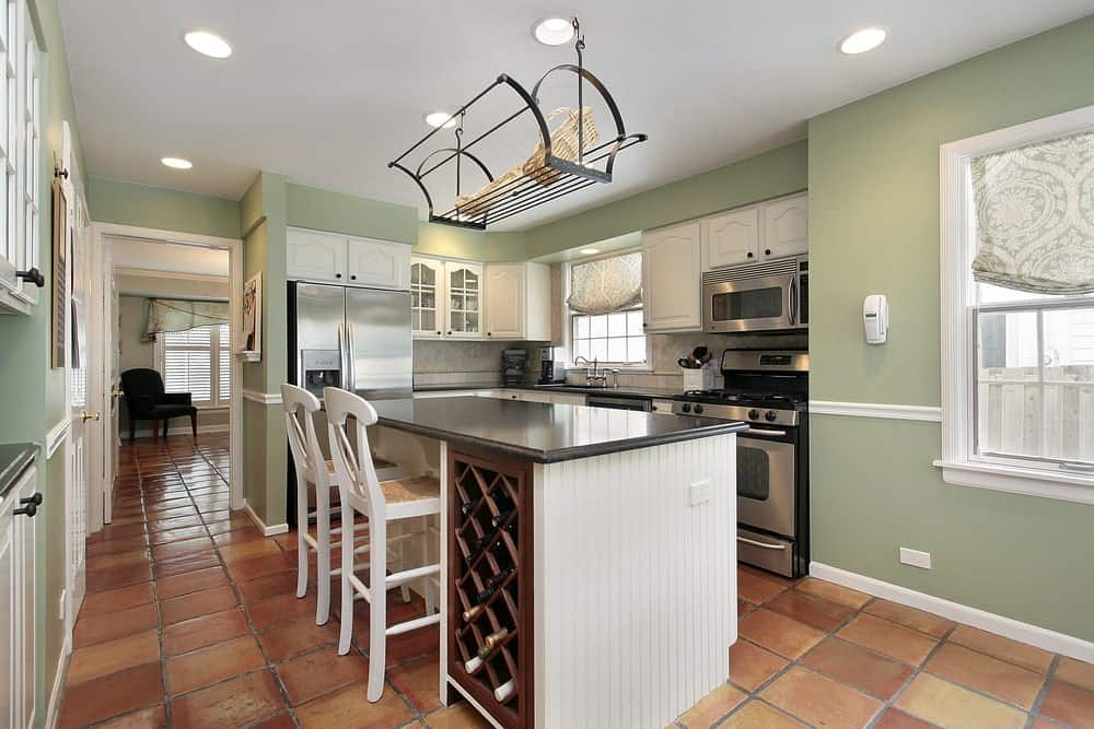 A kitchen with tiles flooring and green walls, along with a breakfast bar with a black granite countertop.