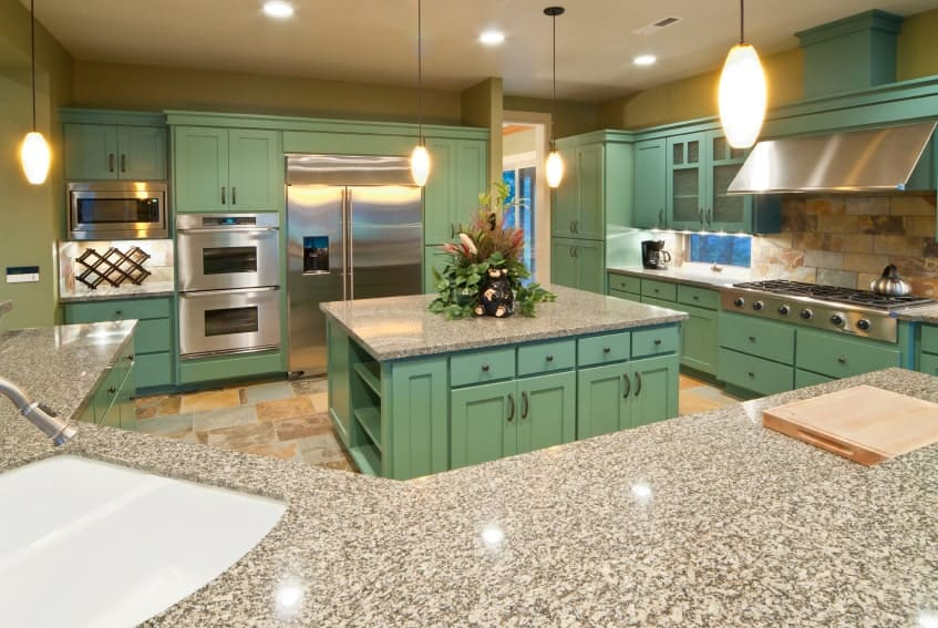 This kitchen features marble countertops on both green kitchen counters and center island. The area is lighted by pendant lights.