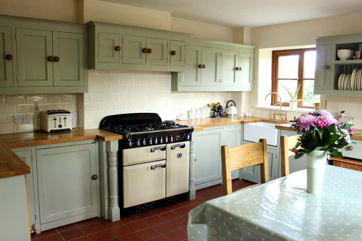 A small kitchen area featuring reddish tiles flooring and green cabinetry and kitchen counters.