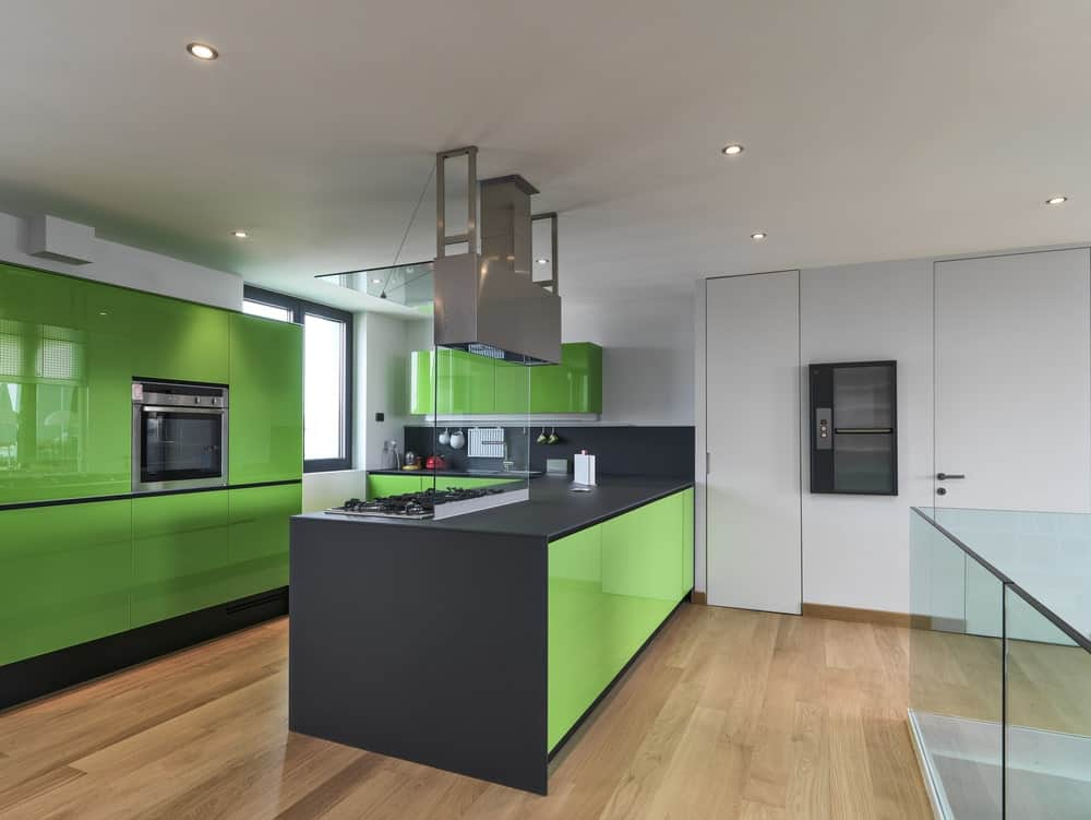 This kitchen features green kitchen counters and cabinetry along with matte black countertops and backsplash.