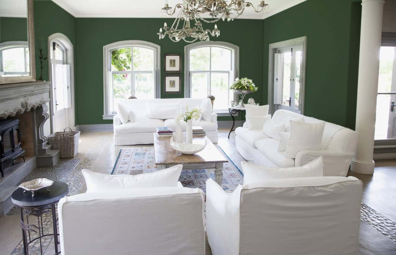 A living room with white seats and a large fireplace, along with green walls lighted by a gorgeous set chandelier.