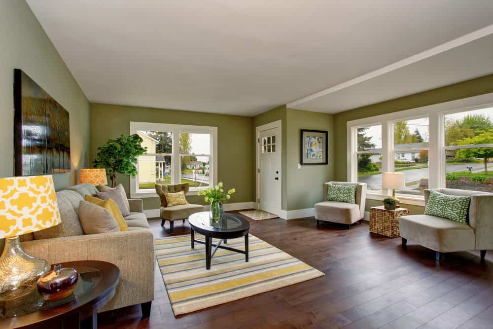 This living room features hardwood flooring and green walls, along with a regular white ceiling.