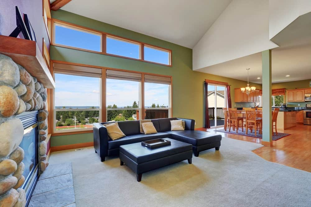 Large great room with hardwood flooring and green walls. The area offers a living space near the stone fireplace.