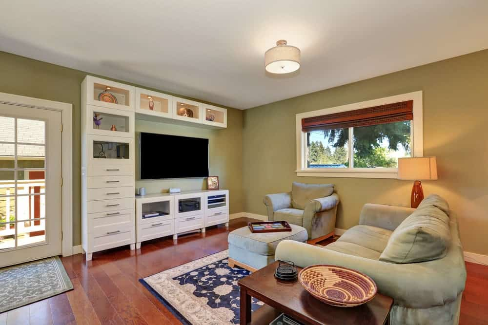 This living room offers a nice couch and a chair along with an ottoman in front of the widescreen TV on the green wall.