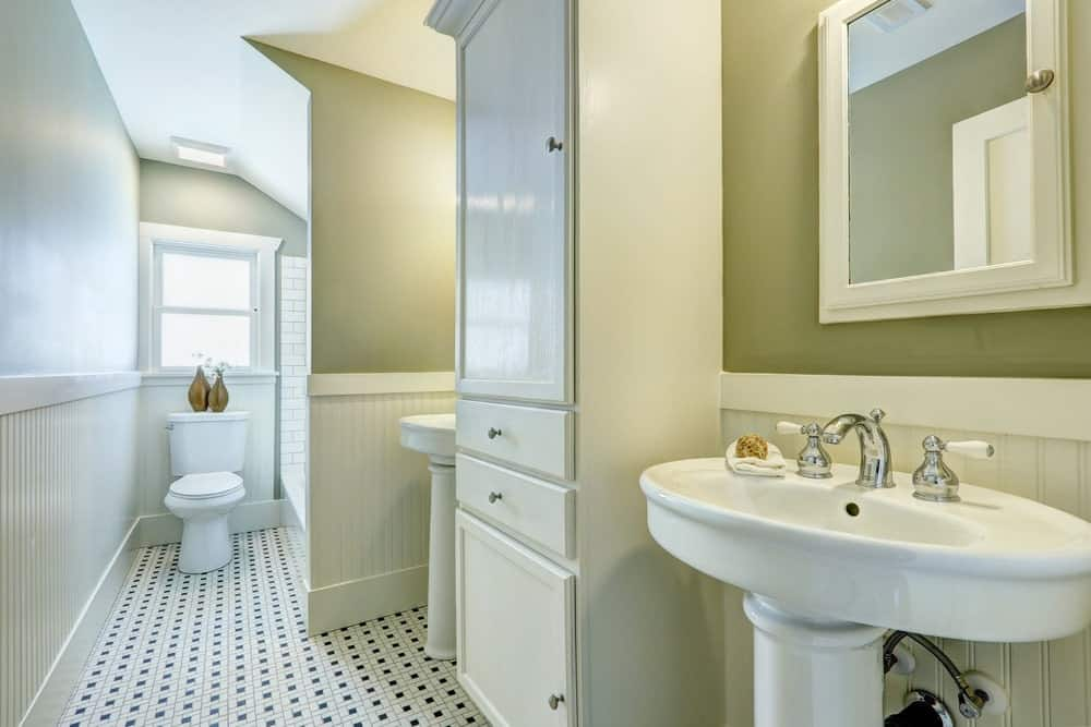 Small primary bathroom featuring a toilet area, a corner tub and two pedestal sinks surrounded by green walls with a white accent.