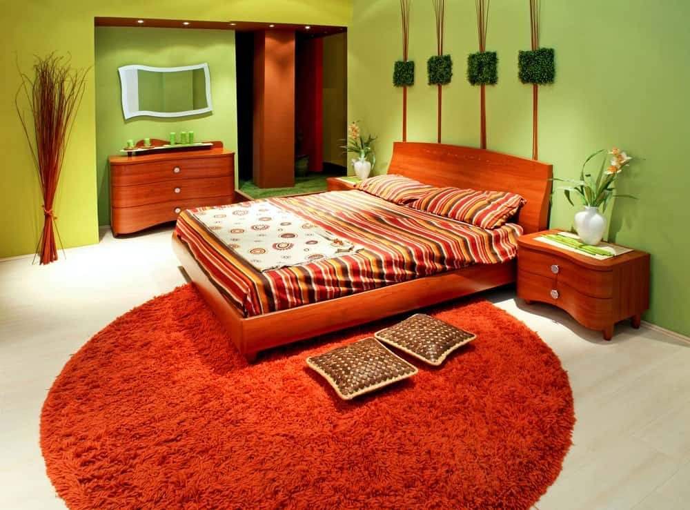This charming primary bedroom has avocado green walls paired with rustic elements of wicker. Above the wooden headboard of the traditional bed is a wall artwork that has square pieces of faux grass paired with wicker. The large orange fur area rug under the bed pops out against the white flooring.