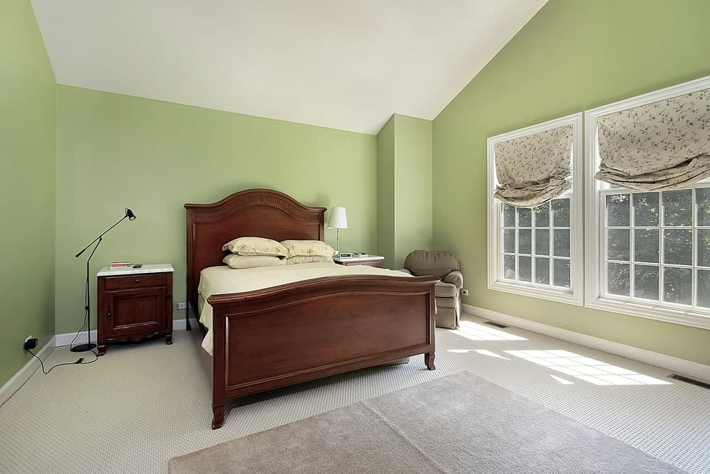 The traditional wooden bed has a built-in headboard of the same wooden make that provides a nice dark contrast to the avocado green walls. These green walls are paired well with a white shed ceiling and white woven carpeted flooring.