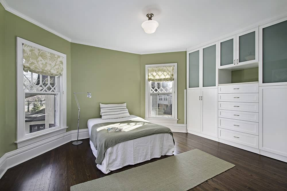 The white cottage-style bed is flanked by two tall windows with ornate white wooden designs. The dark wooden flooring is a nice earthy complement to the green walls and contrasts with the white built-in cabinets and drawers dominating one wall.