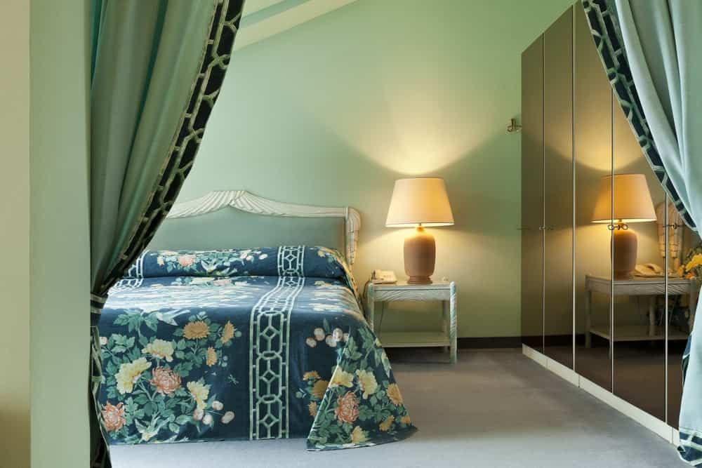 The traditional bed has a nice green chic bedsheet that complements the French headboard paired with white bedside tables that has a table lamp. This lamp shines a warm yellow light the green walls that contrast the sleek black cabinet doors at the side of the bed.