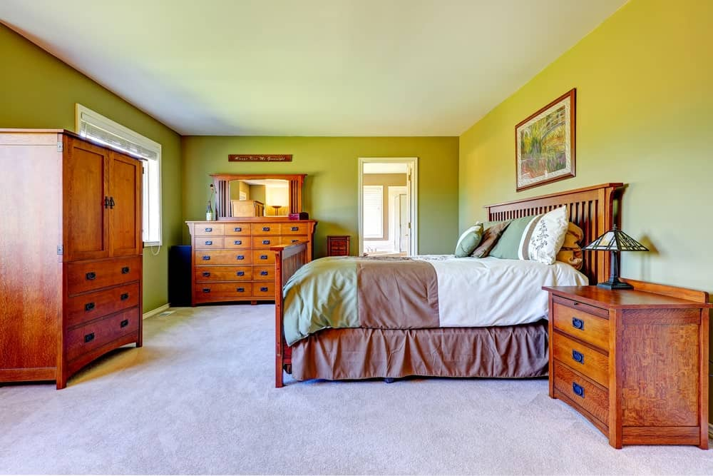 The wooden mission table has a wall-mounted framed artwork above the headboard that pops out against the light green walls. The bedside drawers flanking the bed are perfectly matched with the cabinet and dresser that has a built-in mirror.