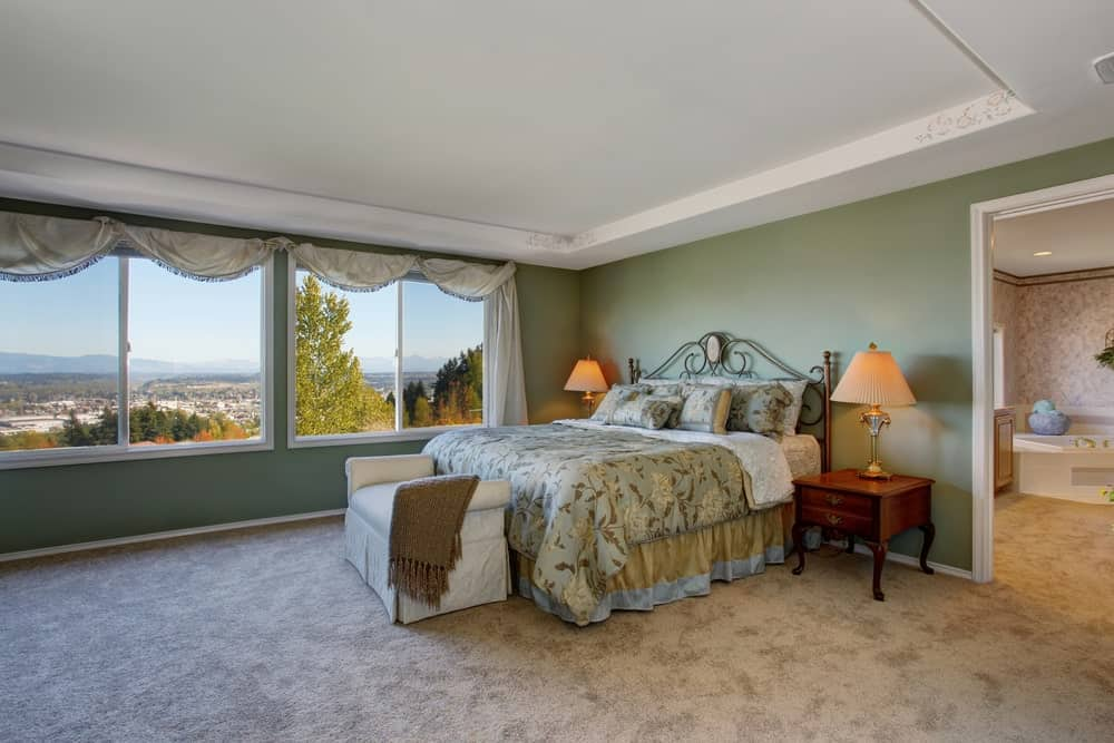 This green-walled primary bedroom offers an amazing view of the surrounding nature through its pair of wide windows that match the white tray ceiling and light gray carpeted flooring. The traditional bed has an ornate iron headboard that matches the patterns of the bedsheets for that chic aesthetic.