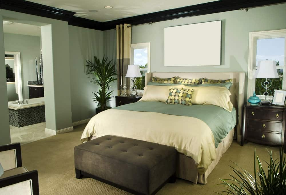 Green primary bedroom with its own bathroom. The room offers a large comfy bed and carpet flooring, along with multiple indoor potted plants.