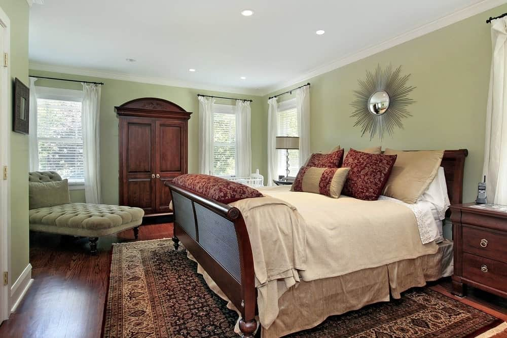A master bedroom with rich hardwood flooring topped by a large area rug surrounded by green walls.