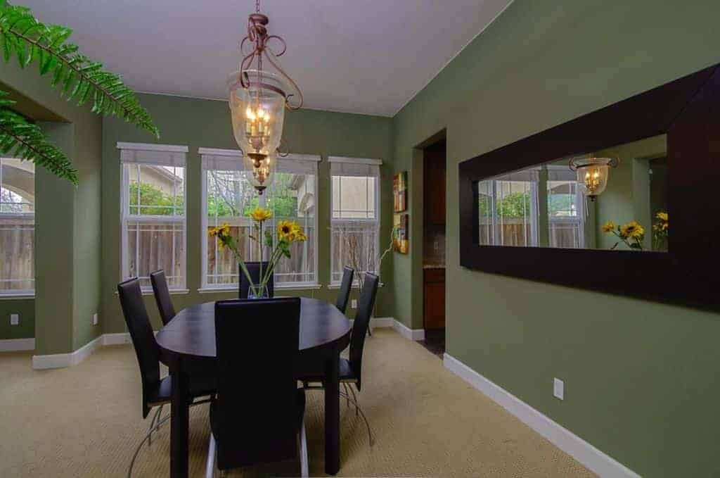 A dining room featuring green walls, carpet flooring and a black dining table set.