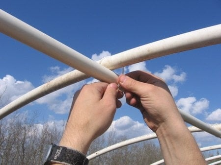 Tying a zip tie on a greenhouse frame.