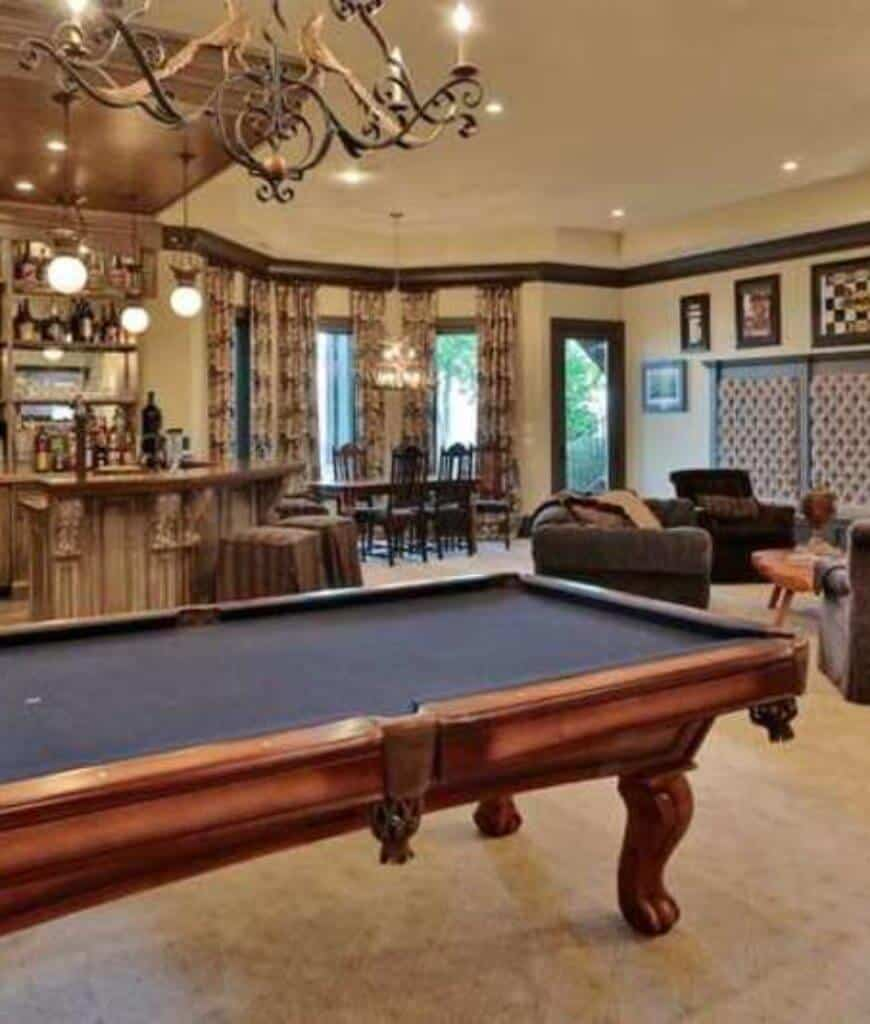 An open concept room offering a clawfoot pool table illuminated by an ornate candle pendant along with recessed lights mounted on the white tray ceiling lined with dark wood crown molding.