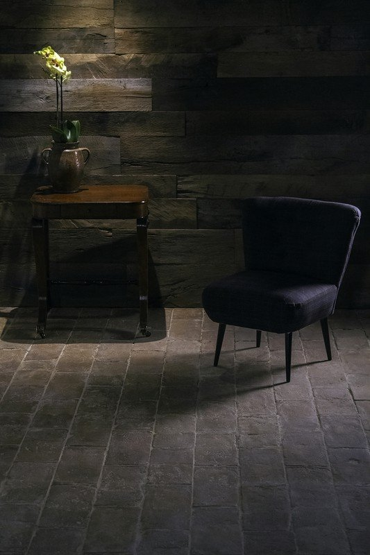 Dark terracotta brick tiles floors with a chair on top of it along with a small side table.