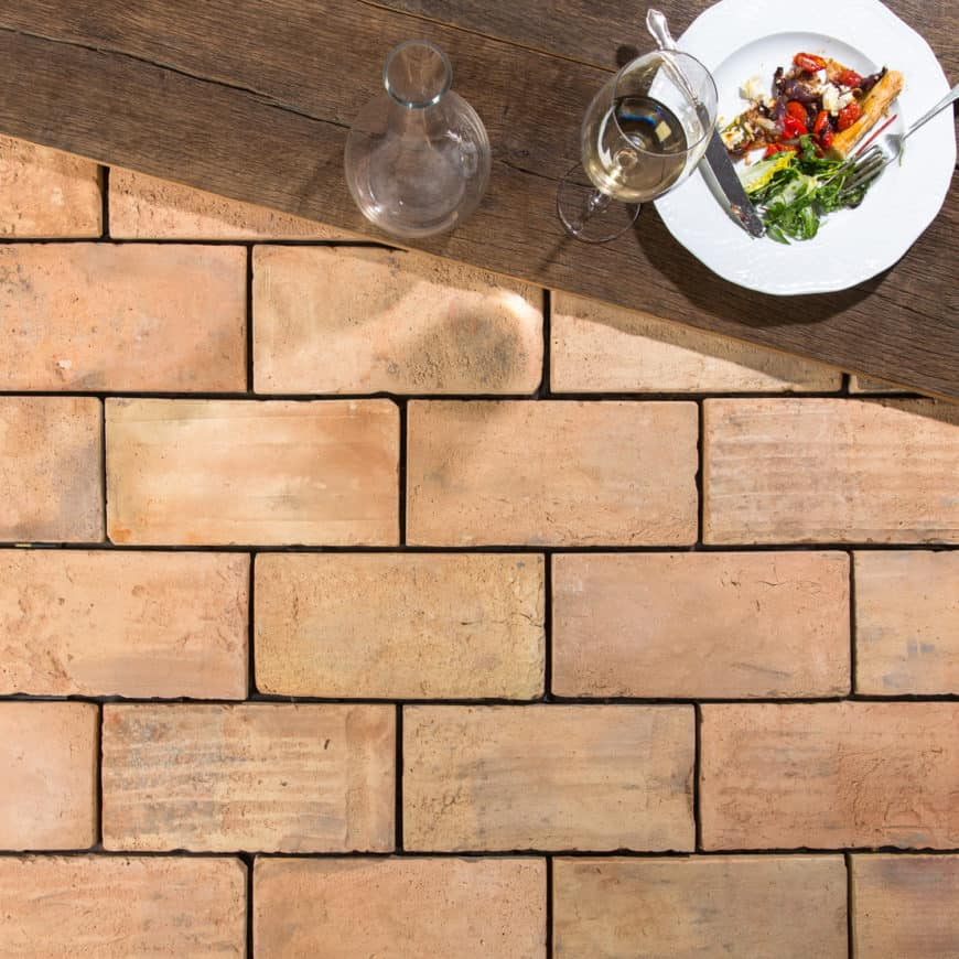 Pale terracotta brick tiles floors with a table on top. The table has a single plate and a wine glass.