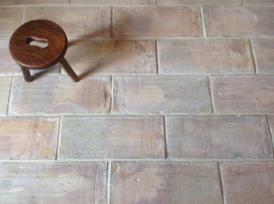 Pale terracotta brick tiles flooring topped by a tiny stool.