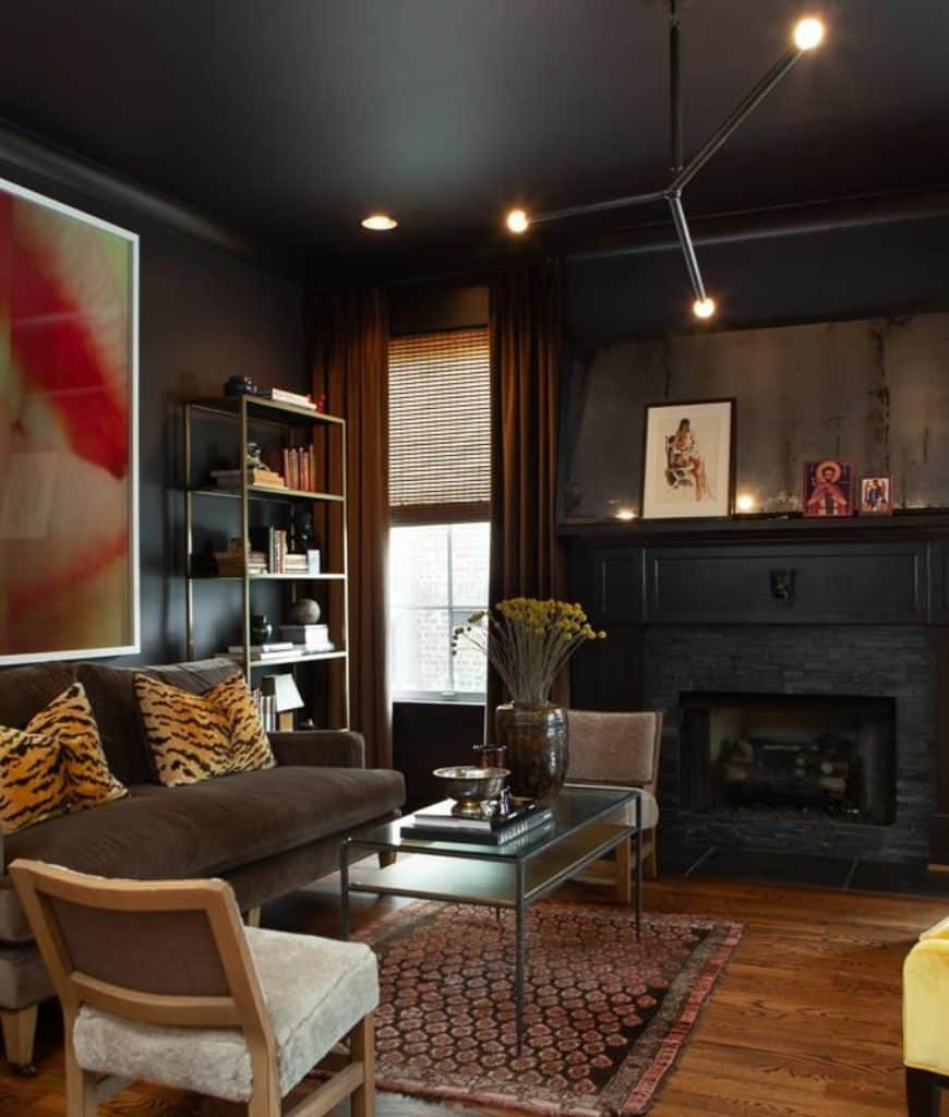 Black living room with comfy seats and a metal coffee table that complements with the open shelving filled with books. It includes contemporary chandelier and a brick fireplace framed with black mantel.