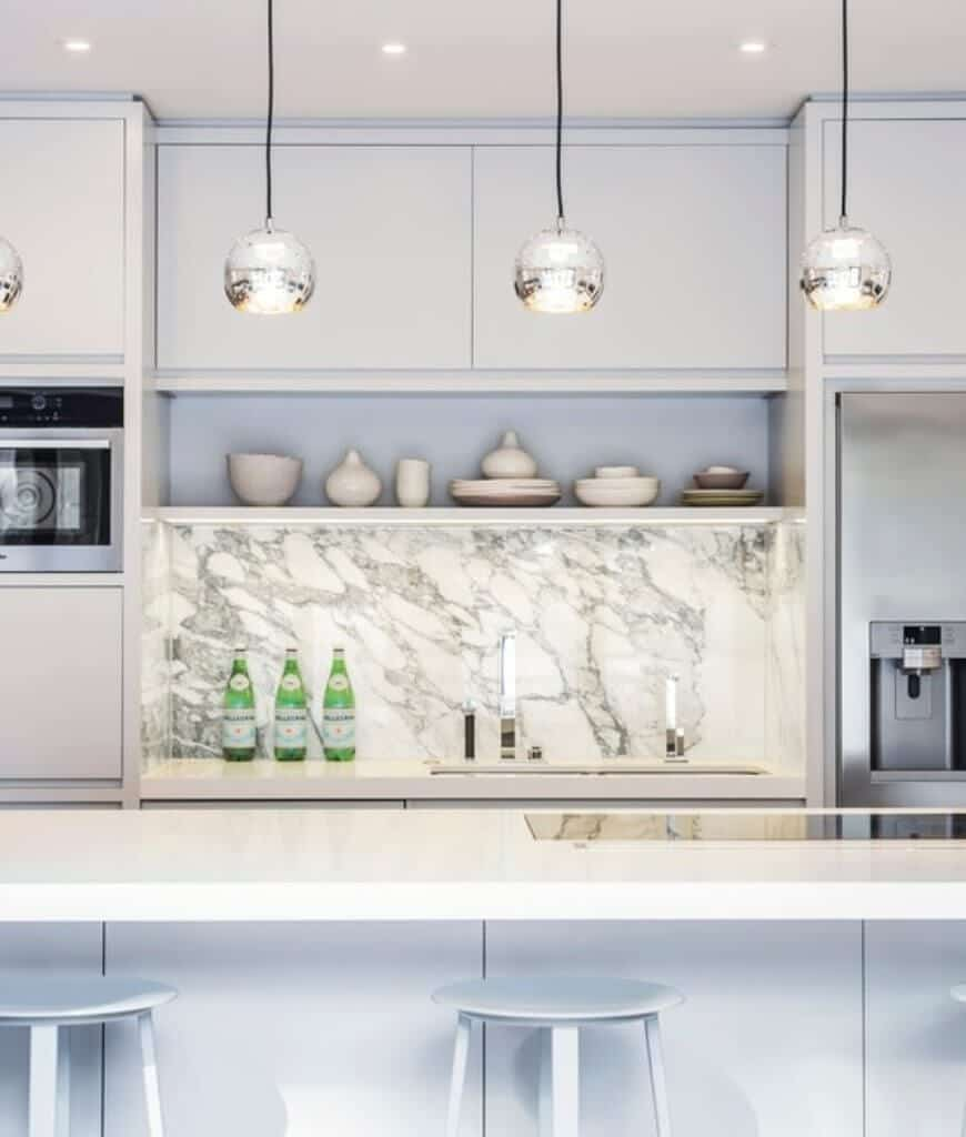 Elegant white kitchen boasts sleek cabinetry accented by a marble backsplash along with a breakfast bar illuminated by fancy globe pendants and recessed ceiling lights.