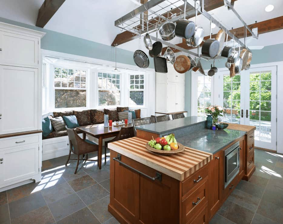 Airy kitchen with a french door that opens to the patio and a window seat nook filled with brown and blue pillows. It includes a wooden dining set, a breakfast island with a raised eating counter and a stainless steel pot rack fixed to the wood beams.