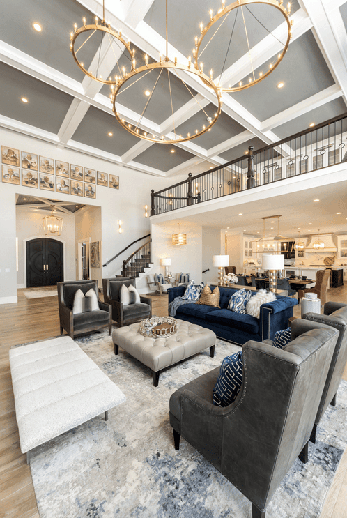Transitional living room accented with huge round pendants that hung from the gray coffered ceiling. It has a deep blue velvet sofa, gray velvet wingback chairs and a white bench surrounding a tufted ottoman.
