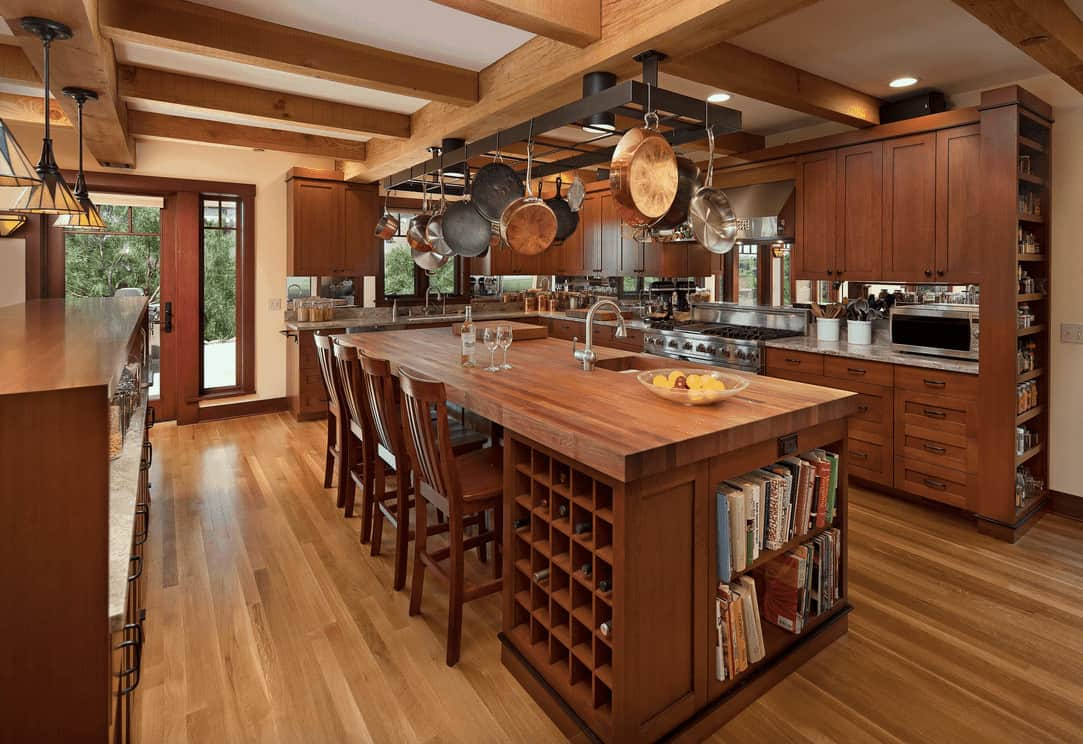 Craftsman kitchen offers rich wood cabinetry and a black metal pot rack that stands over the wooden breakfast island fitted with built-in shelving and wine rack cubbies.