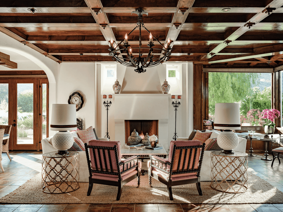 Mediterranean living room incorporated with a symmetrical design. It has a wrought iron chandelier that hung from the wooden coffered ceiling and a marble top coffee table surrounded with white sofas and pink cushioned chairs.