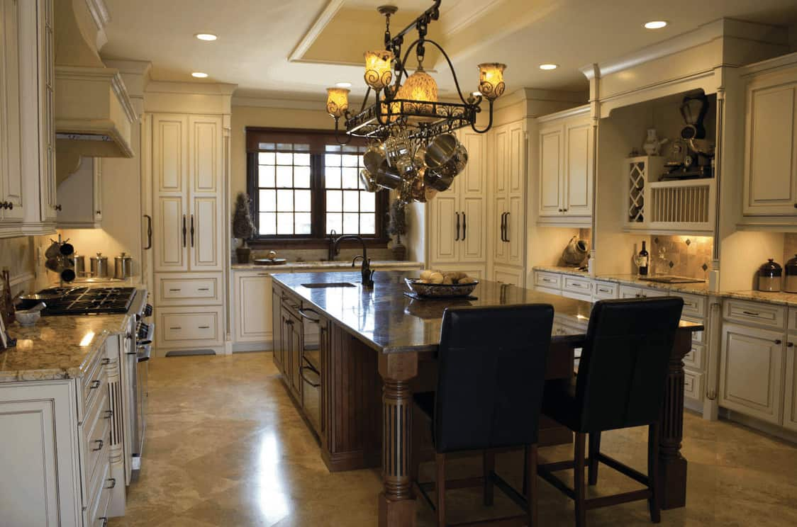 Traditional kitchen boasts an ornate pot rack integrated with light fixture and is suspended over a wooden breakfast island surrounded with white cabinetry.