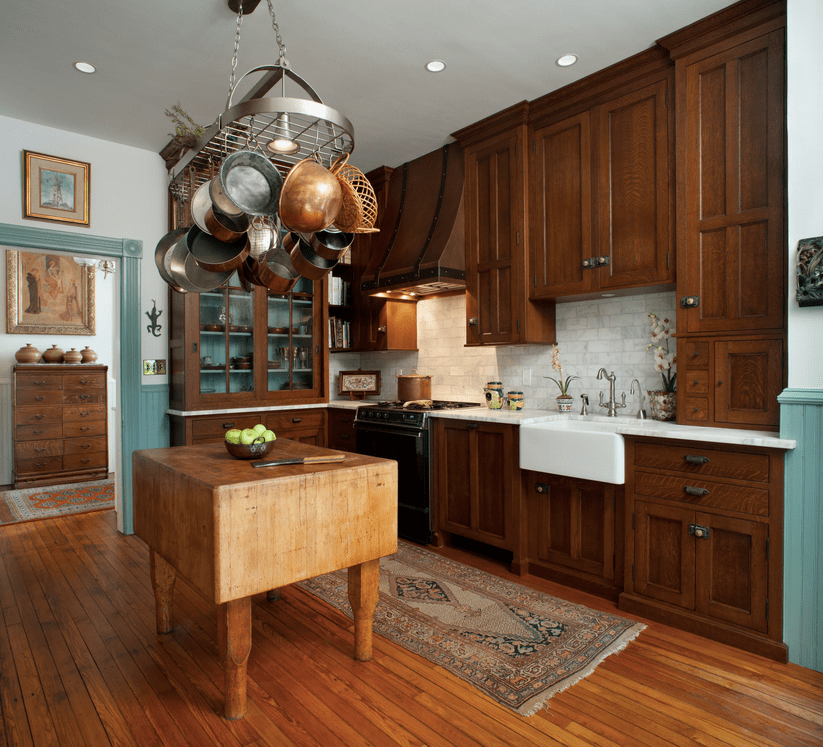 An oval pot rack stands over the wooden counter in this kitchen featuring dark wood cabinetry and display cabinet over wood plank flooring topped by a kitchen runner.