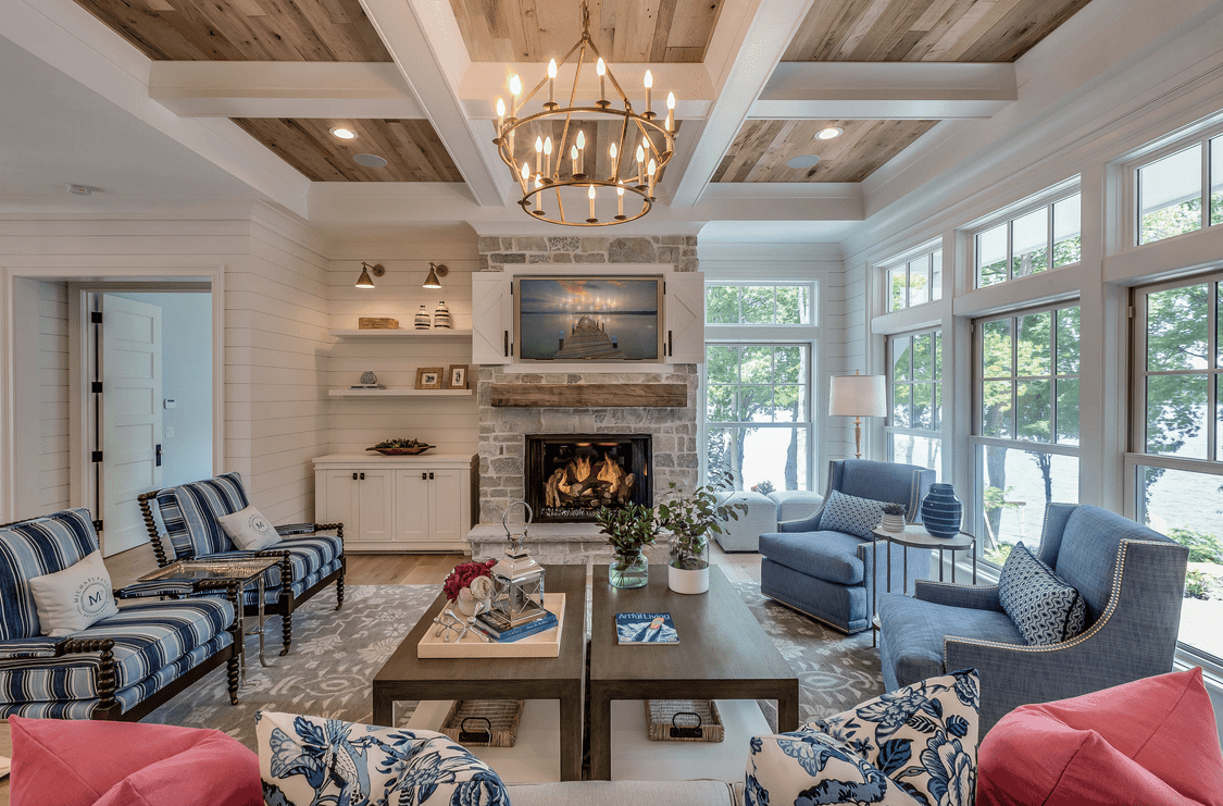 Farmhouse living room illuminated by a brass candle chandelier that hung from the coffered ceiling clad in natural wood planks. It has a stone fireplace and charming mismatched chairs surrounding a pair of wooden coffee tables.
