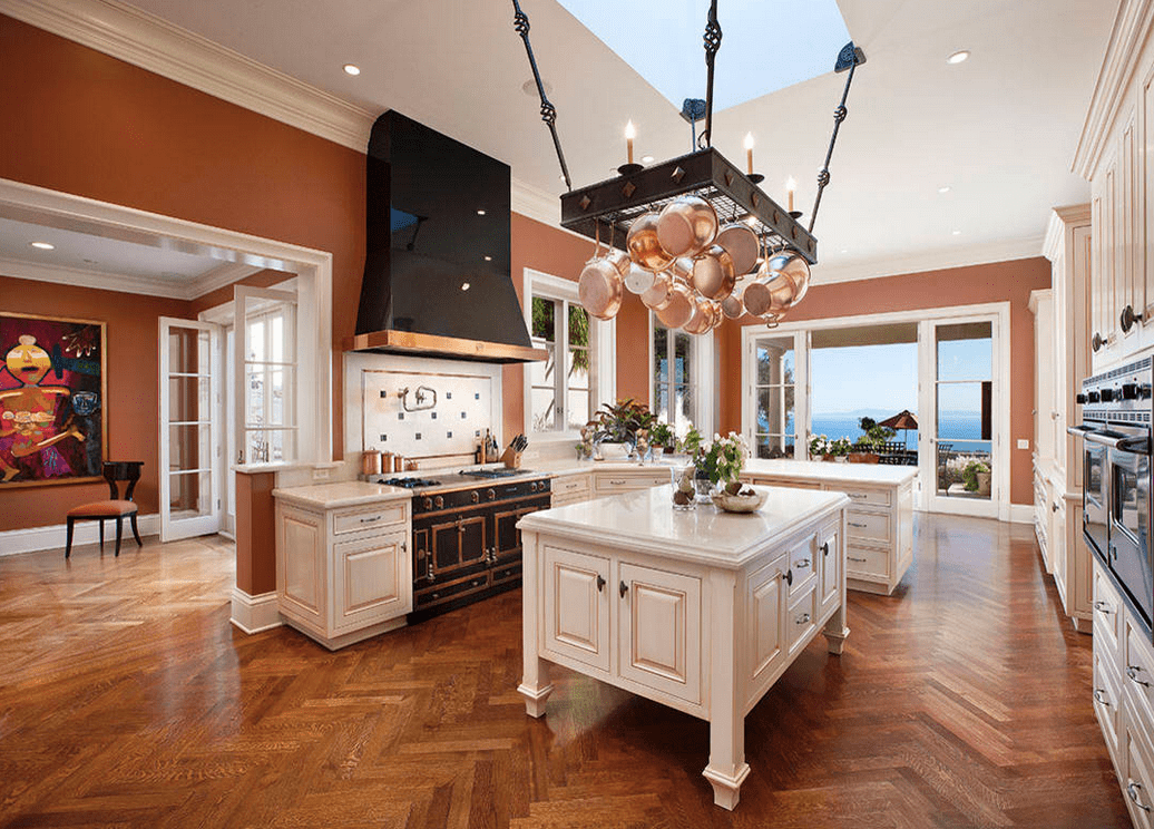 Gorgeous kitchen with white cabinetry contrasted with black range hood and lovely pot rack lined with diamond gems and hung beneath the skylight and over the kitchen island.