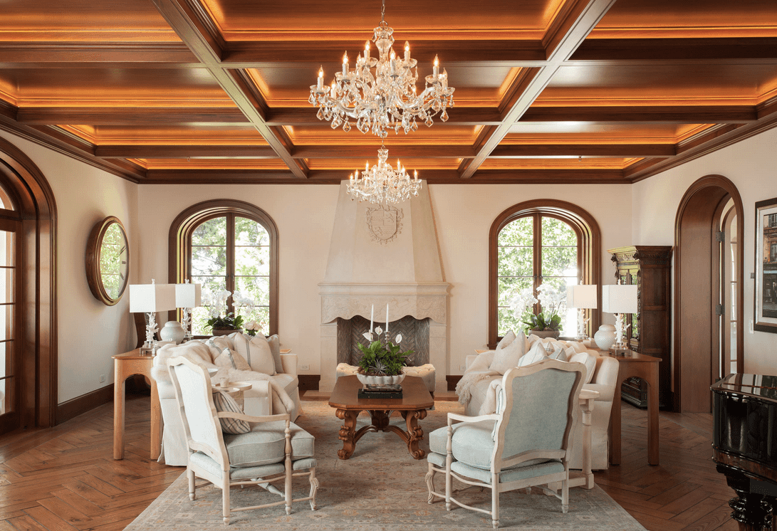 Traditional living room showcases herringbone wood flooring topped by a vintage rug and wooden coffered ceiling with hanging crystal chandeliers.