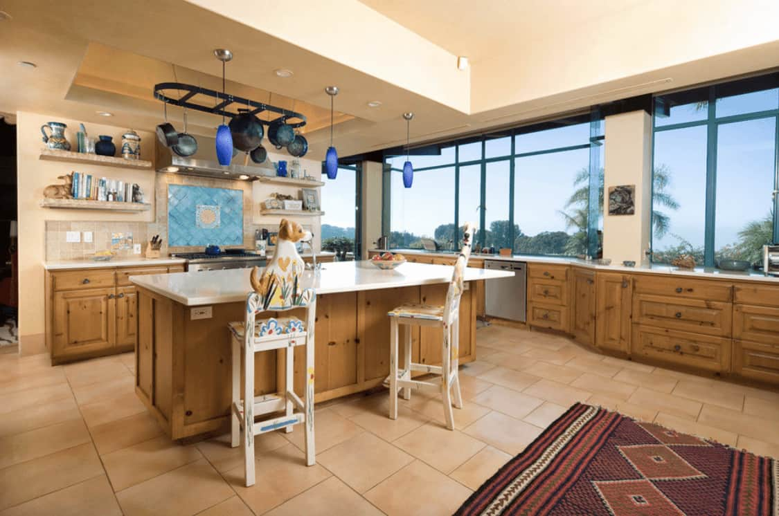 Southwestern kitchen features wooden cupboard and breakfast island paired with animal counter chairs along with a black pot rack and panoramic windows overlooking the outdoor scenery.