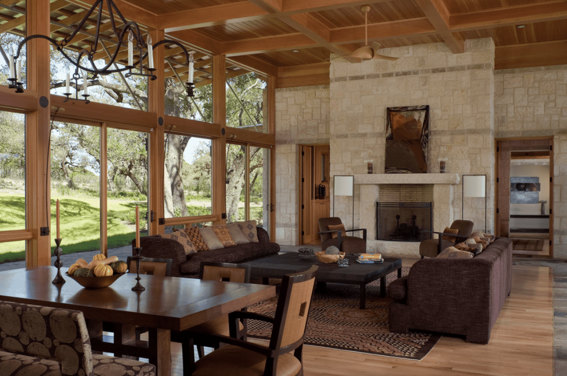 Rustic living room with stone brick wall and full height glazing overlooking a serene outdoor view. It has a brown sofa set and stone fireplace lighted by white floor lamps.