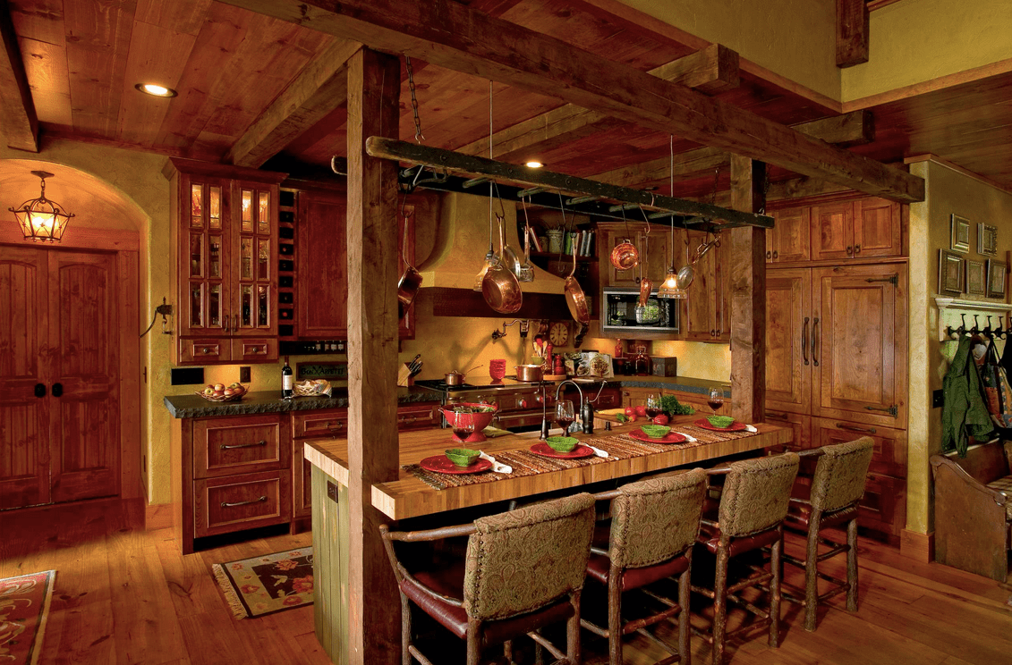 Cozy kitchen showcases wooden cabinetry and a breakfast island lined with wood beams and pot rack that resembles a ladder.