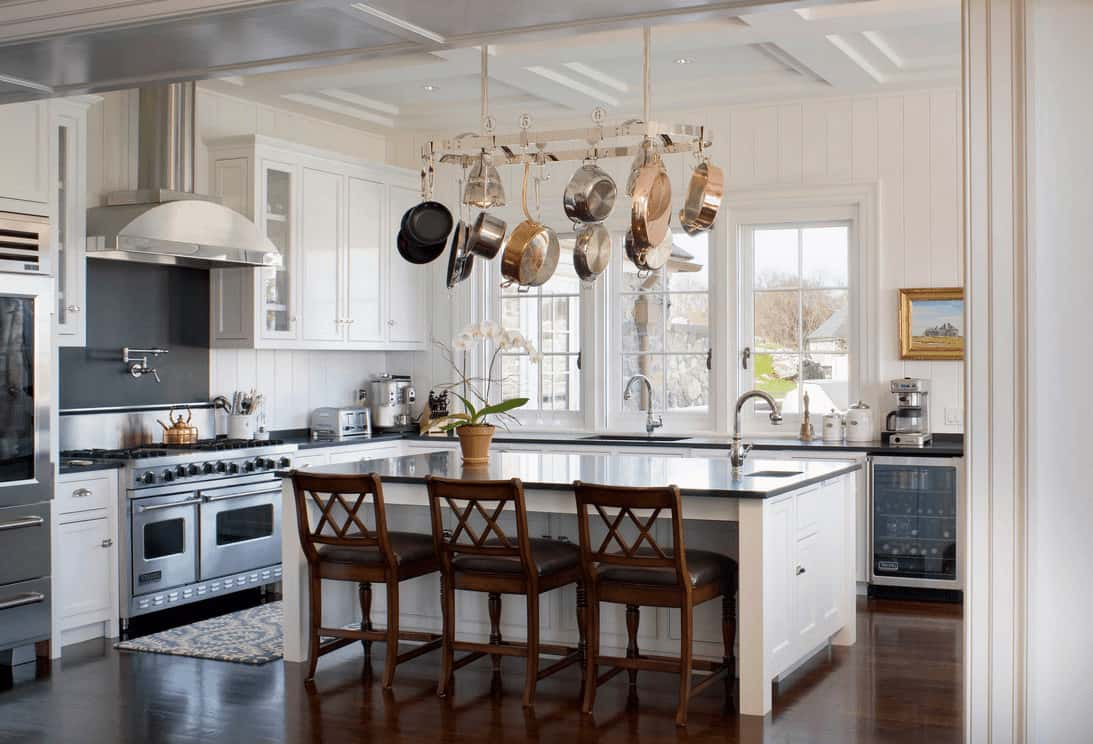 White kitchen with beadboard wall and coffered ceiling with a hanging stainless steel pot rack. It has a kitchen island topped with a black granite counter and lined with wooden chairs.