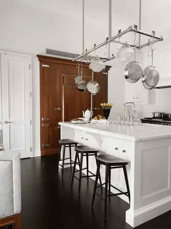 A wooden storage cabinet stands out in this white kitchen boasting a stainless steel pot rack that hung over the breakfast island with black chairs and a sink fitted with chrome fixtures.