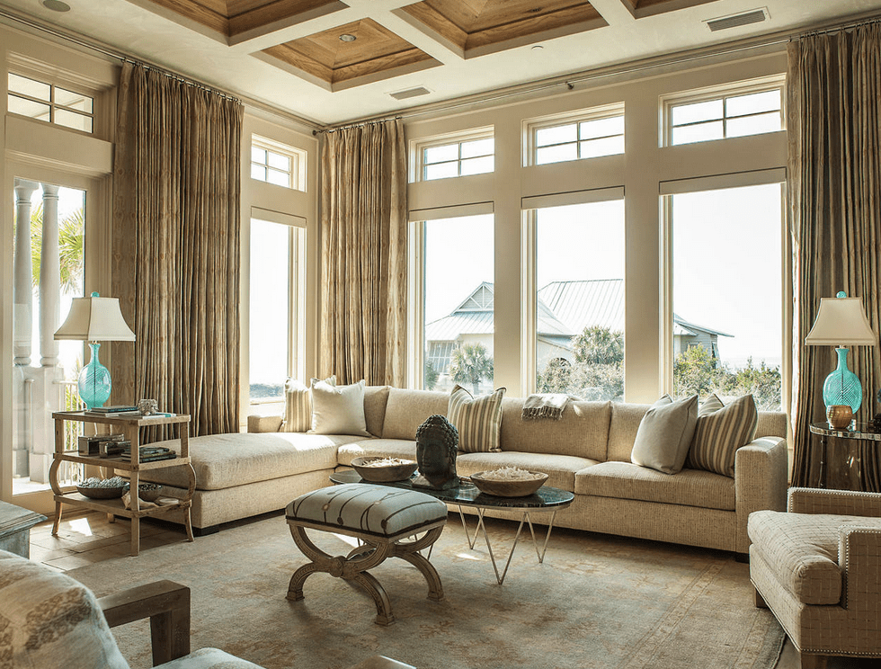 Sophisticated living room features a wooden coffered ceiling and glass paneled windows covered with beige draperies. It has a metal coffee table and L-shaped sectional filled with gray and striped pillows.