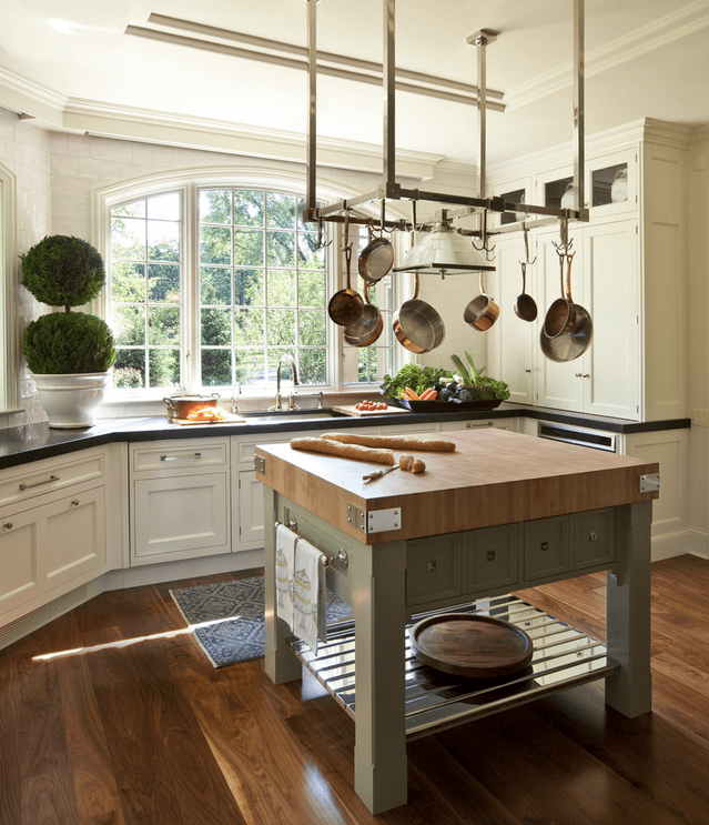 Natural light streams through the arched windows in this kitchen with white cabinetry and metal pot rack suspended over the kitchen island that sits on wide wood plank flooring.