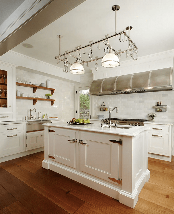 Sleek white kitchen illuminated by a pair of glass dome pendants attached to the stainless steel pot rack that hung over the marble top kitchen island fitted with a sink and faucet.