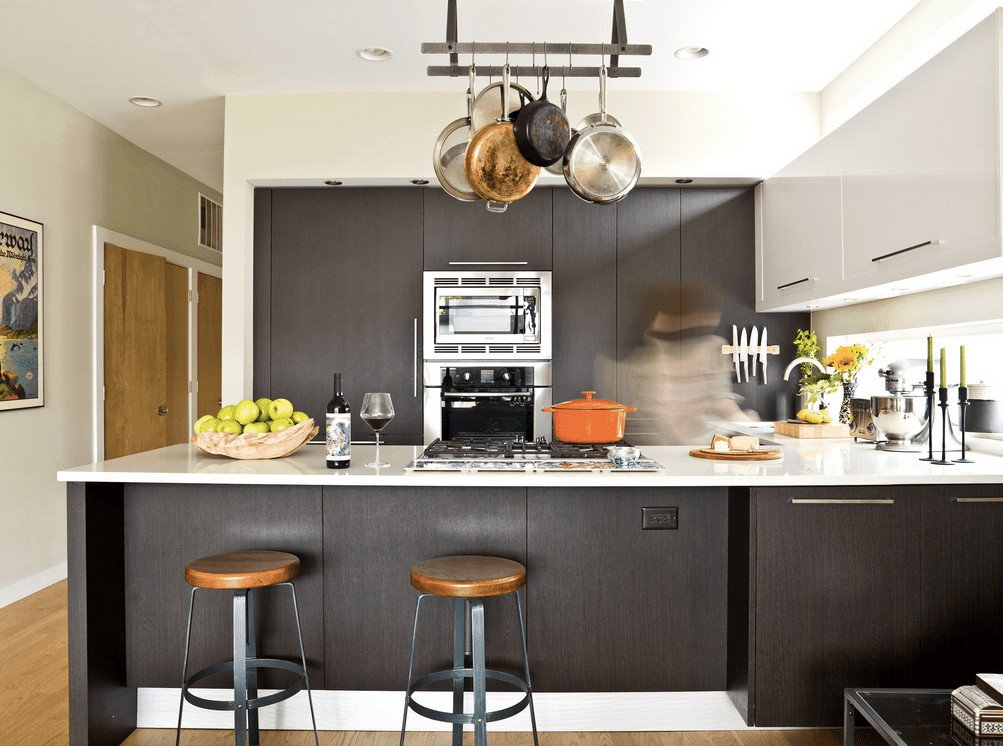 Contemporary kitchen showcases dark wood storage and peninsula beautifully contrasted with white upper cabinetry and countertop. It has stainless steel appliances and metal pot rack with s hooks.