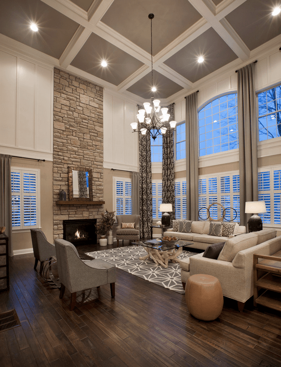 Traditional living room showcases a wood plank flooring and a high coffered ceiling with recessed lights and a hanging chandelier. It has a stone fireplace lined with a wooden mantel that's topped with a mirror.