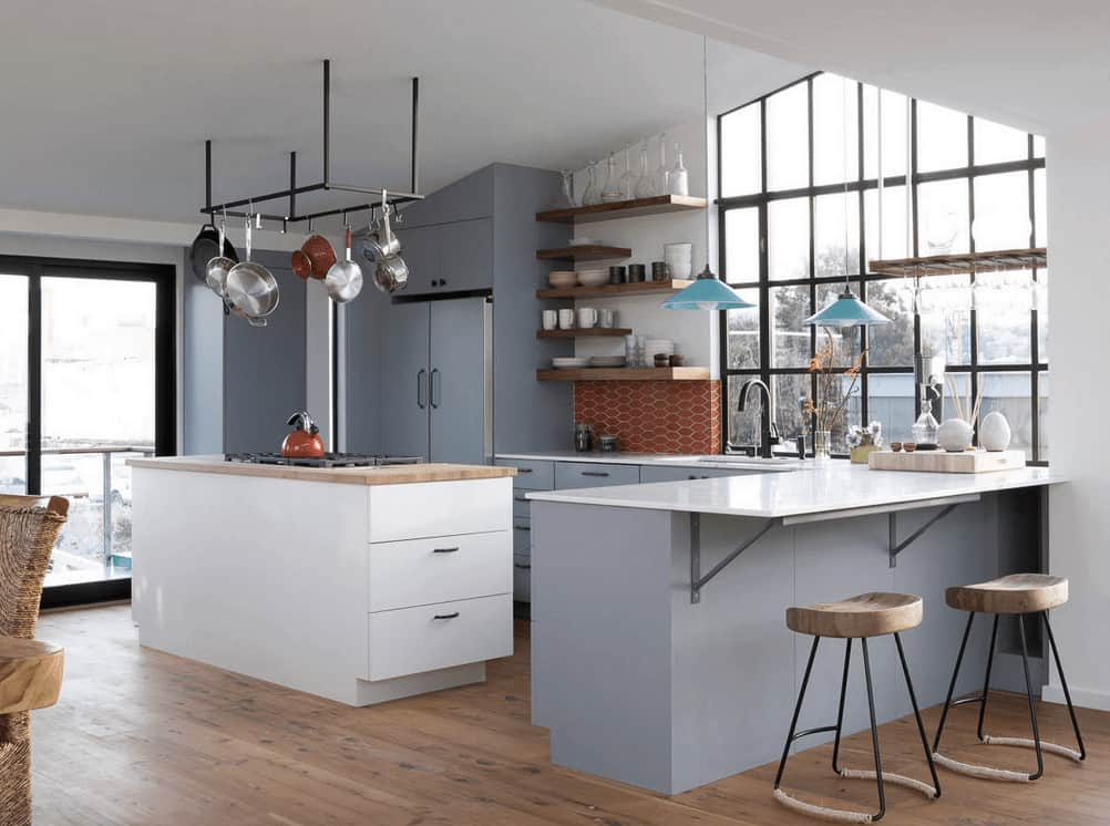 A pair of wooden stools sit at the dusty blue peninsula matching with the cabinetry in this modern kitchen with white island bar that sits underneath the wrought iron pot rack.