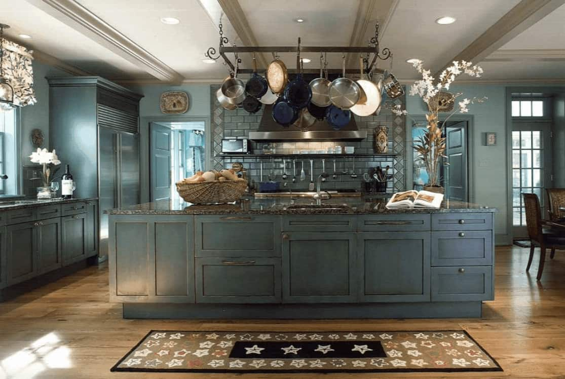Marvelous kitchen with a white ceiling lined with gray beams and hardwood flooring topped with a star pattern kitchen runner. It includes a rectangular pot rack with hanging stainless steel and blue pots.