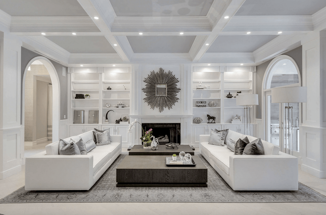 Gorgeous white living room decorated with a sunburst mirror mounted above the fireplace. It has wooden coffee tables in between sleek facing sofas lighted by floor lamps and recessed lights that are fixed to the coffered ceiling.