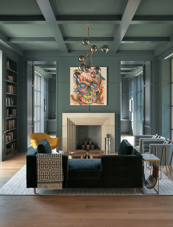 This living room is designed with a colorful wall art and a contemporary chandelier that hung from the coffered ceiling. It has a dark velvet sofa, gray round back chairs and a yellow accent chair that sits next to the fireplace.
