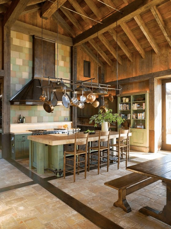 Rustic kitchen with green cupboard and island bar sitting beneath a metal pot rack that hung from the high cathedral ceiling. It includes a large vent hood that's fixed to the mosaic backsplash tiles.