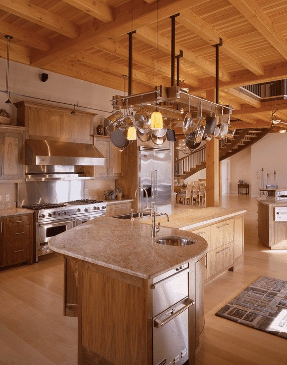 Farmhouse kitchen offers light wood cabinetry and breakfast island that complements with the hardwood flooring. The continuity of wood elements from the beamed ceiling and pot rack creates a unified look.